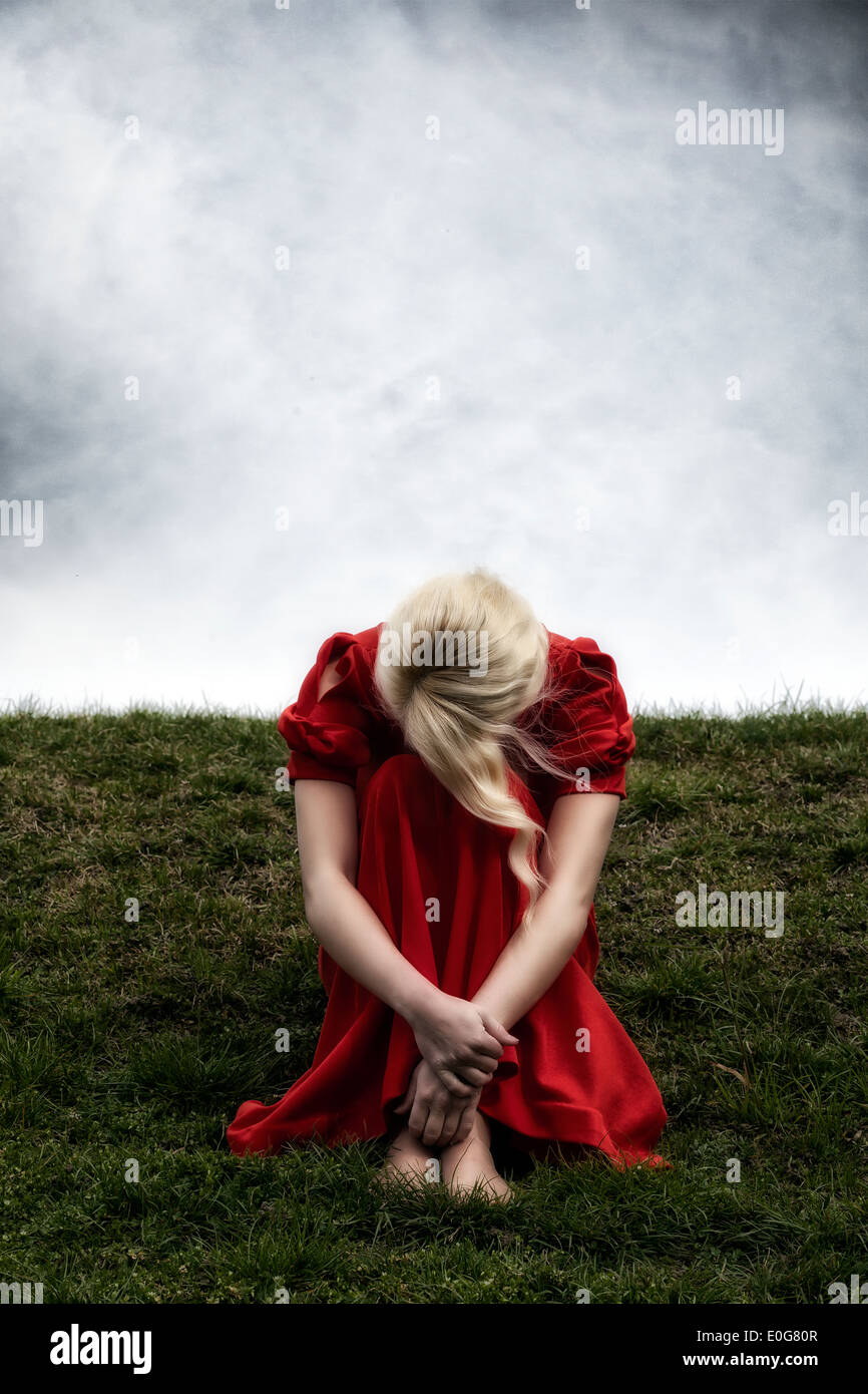 a woman in a red dress is sitting on a hill - Stock Image