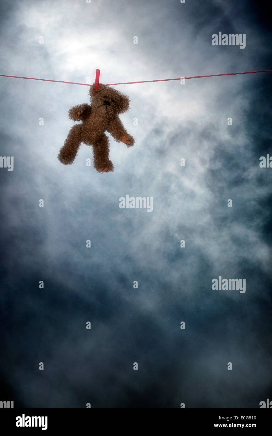 a teddy bear on a clothes line - Stock Image