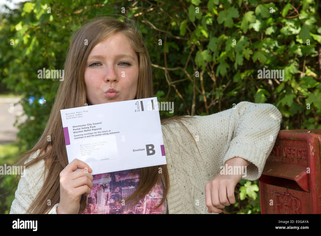 Silchester, Hampshire, UK. 12th May, 2014. Postal ballot for the May European Parliament Elections arrives. Young voter Hollie Parks from Hampshire kissing her postal vote goodbye at the postbox Credit:  Peter Titmuss/Alamy Live News - Stock Image
