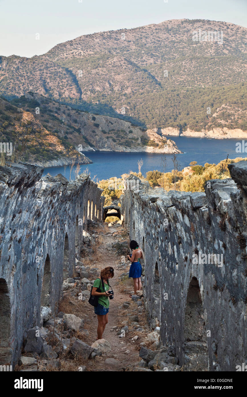 Woman taking photographs of the processional walkway on Gemiler Island in Fethiye gulf, lycian coast, Mediterranean Sea, Turkey - Stock Image