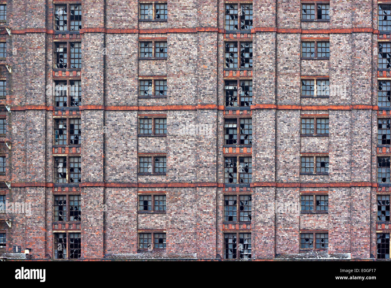 Broken windows in huge derelict warehouse. (Stanley Dock, Liverpool, UK, largest brick built warehouse in the world) Stock Photo