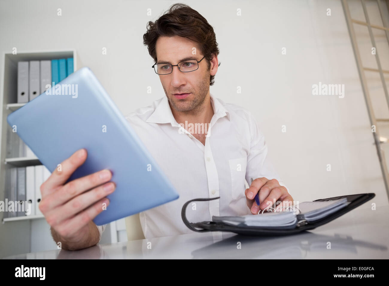 Casual businessman organizing his schedule at his desk - Stock Image