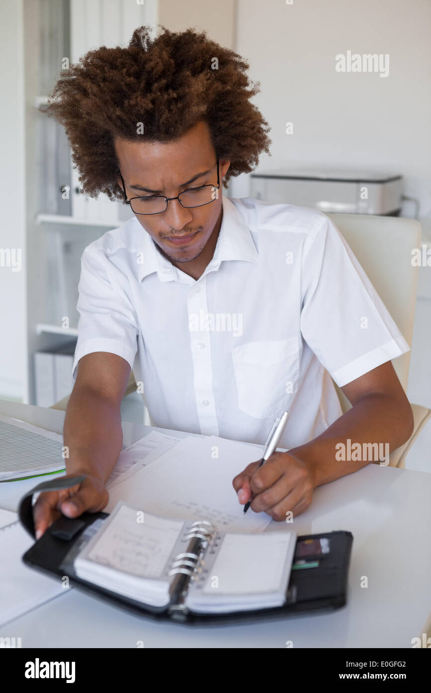 Casual young businessman organizing his schedule at his desk - Stock Image