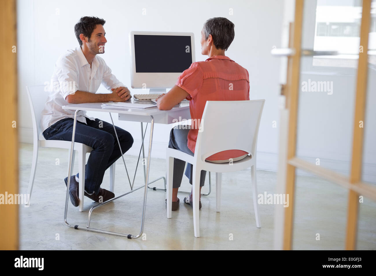 Casual business people talking at desk and smiling - Stock Image