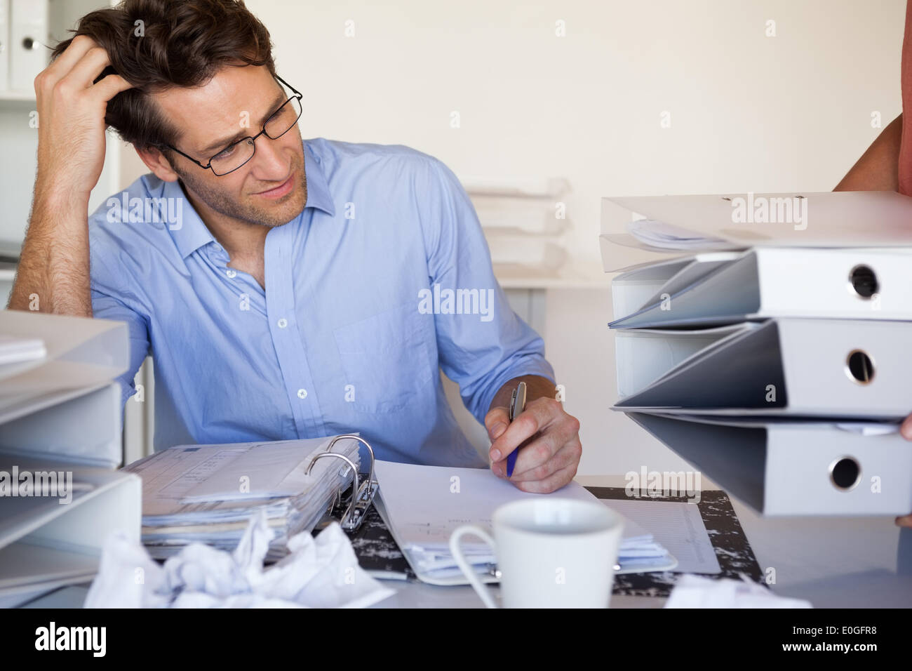 Casual businessmans workload getting bigger and bigger - Stock Image
