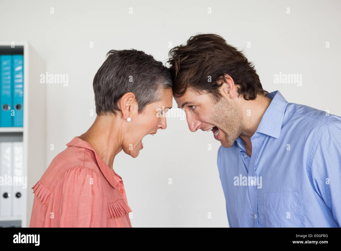 Angry business people shouting at each other - Stock Image