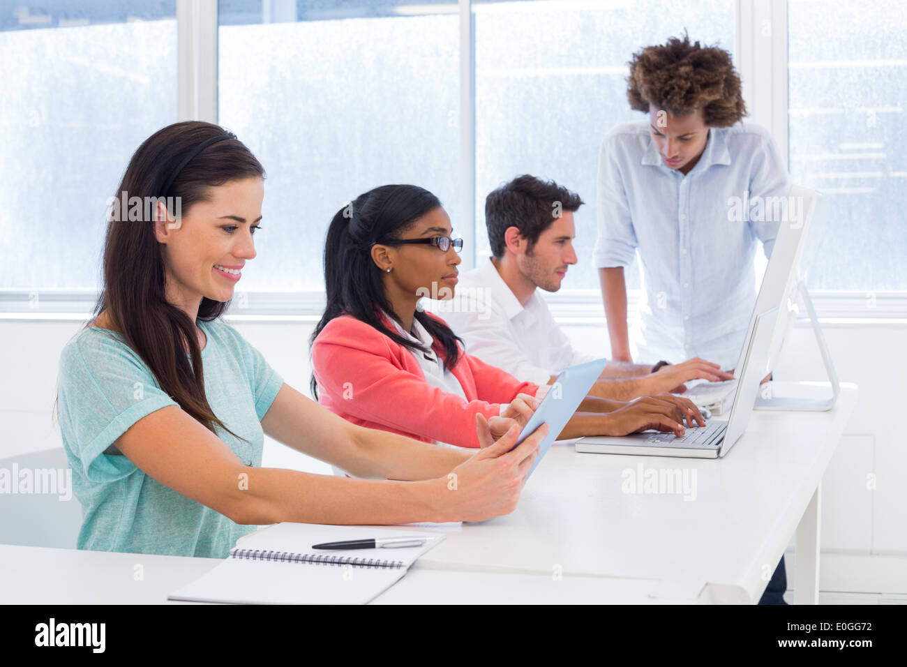 Workers on tablets and laptops Stock Photo