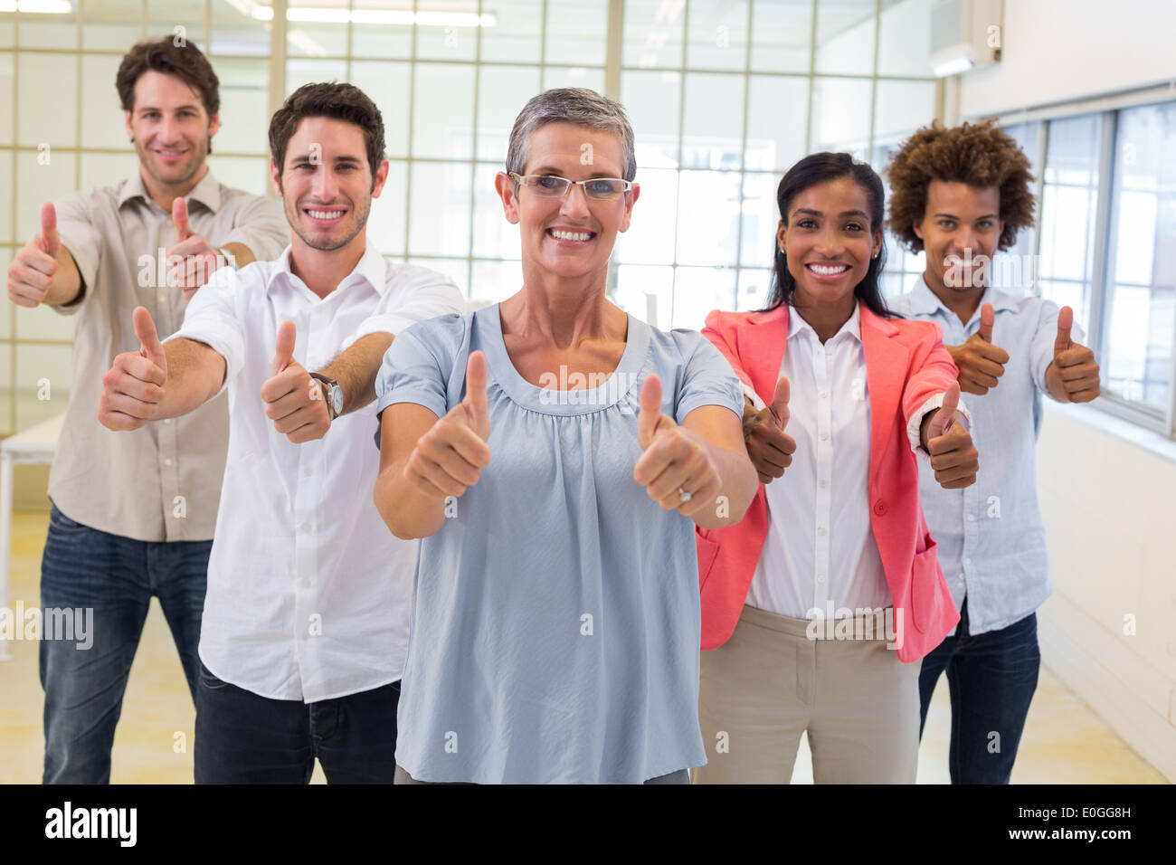 Business people giving thumbs up to camera and smiling - Stock Image