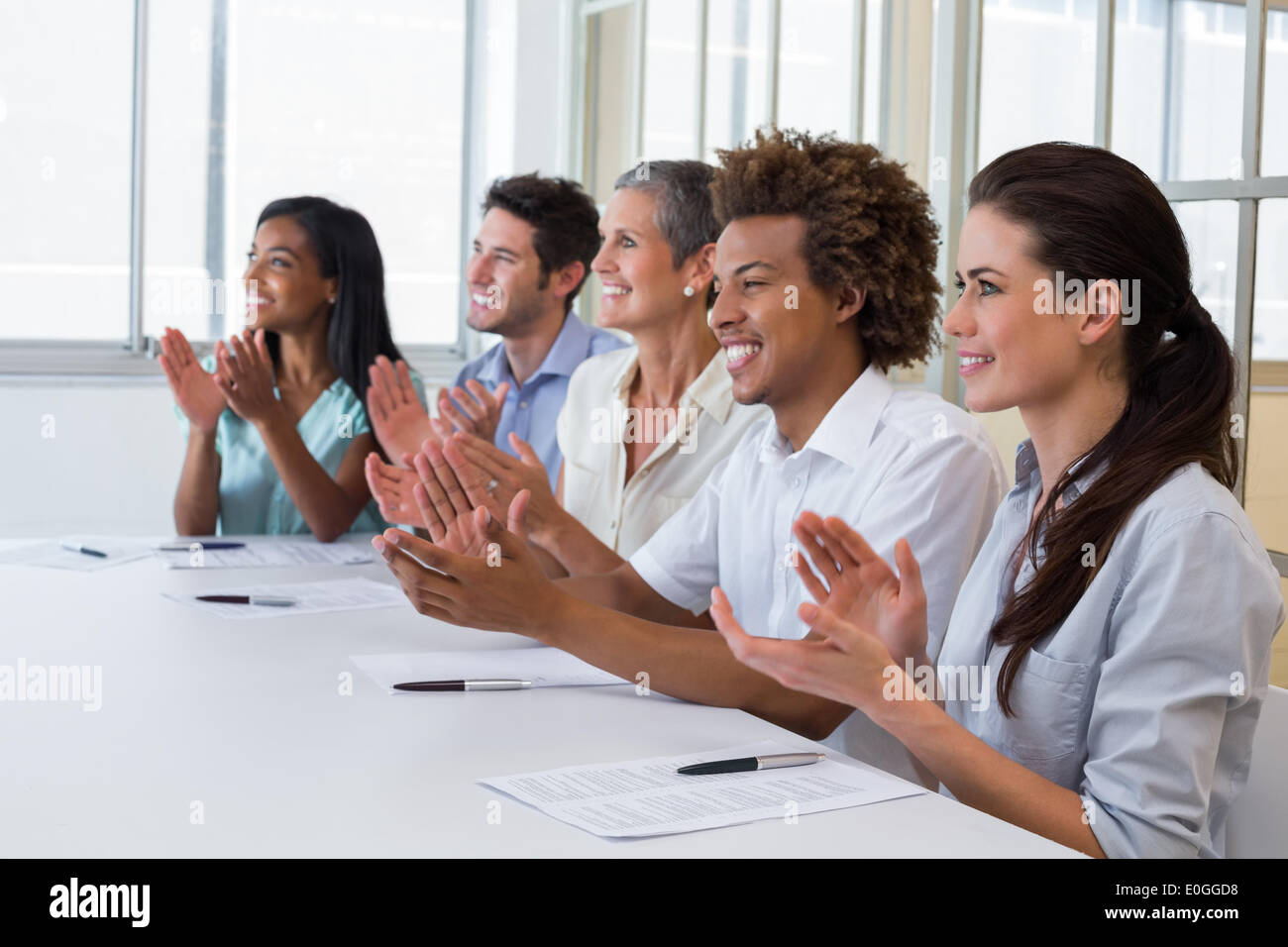 Casual business team clapping at presentation - Stock Image
