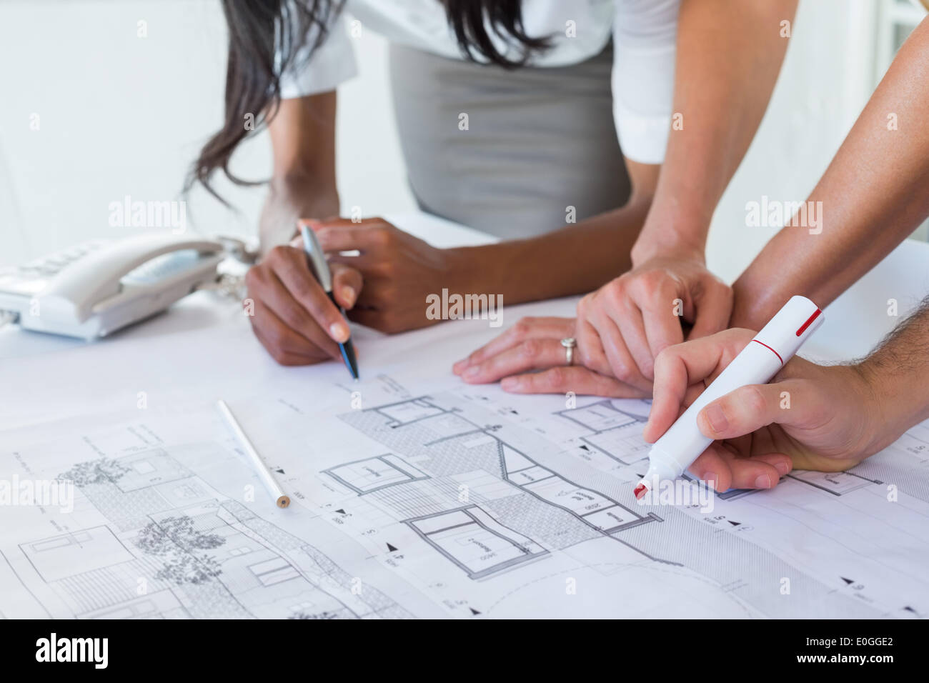 Coworkers working on blueprints together - Stock Image