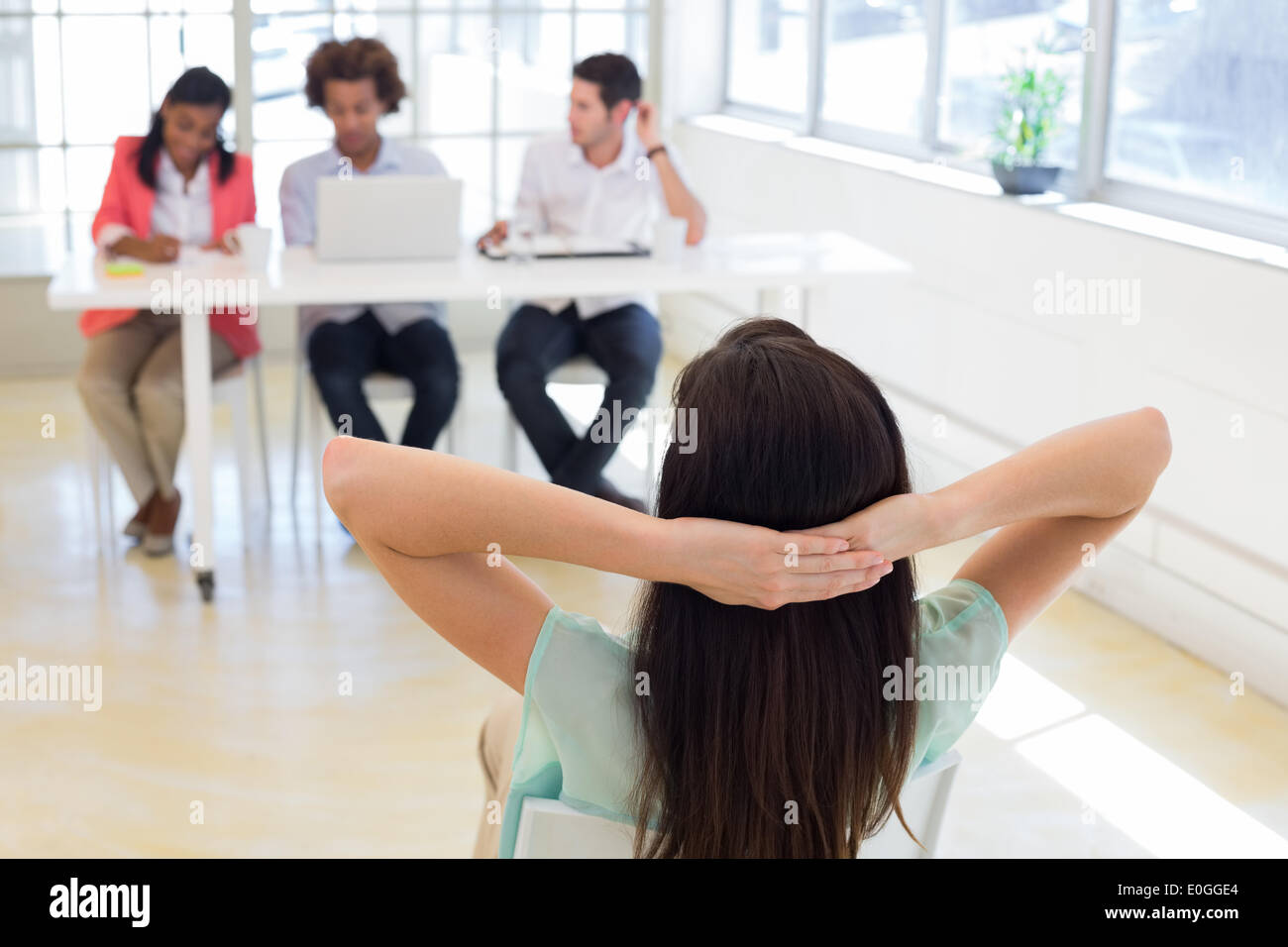 Businesswoman relaxes with hands behind her head - Stock Image