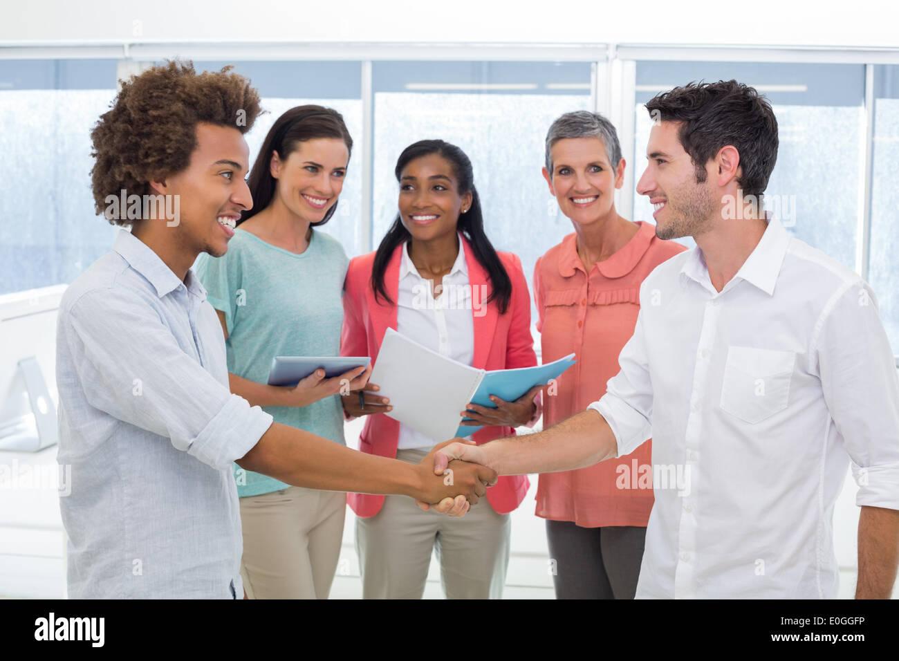 Attractive businessmen shaking hands at work - Stock Image