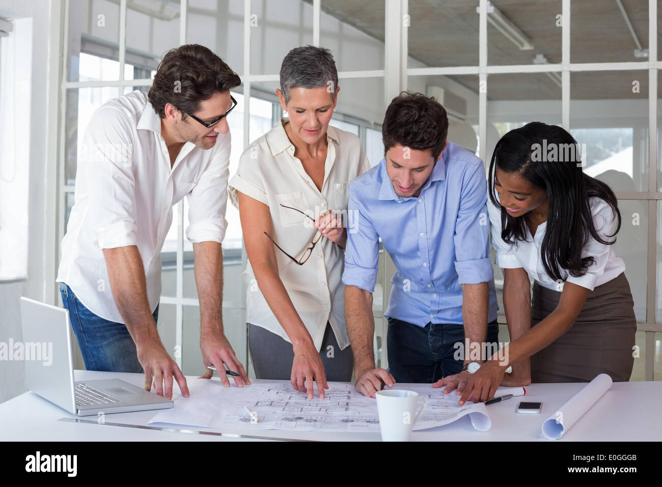 Attractive business people working hard on plans - Stock Image