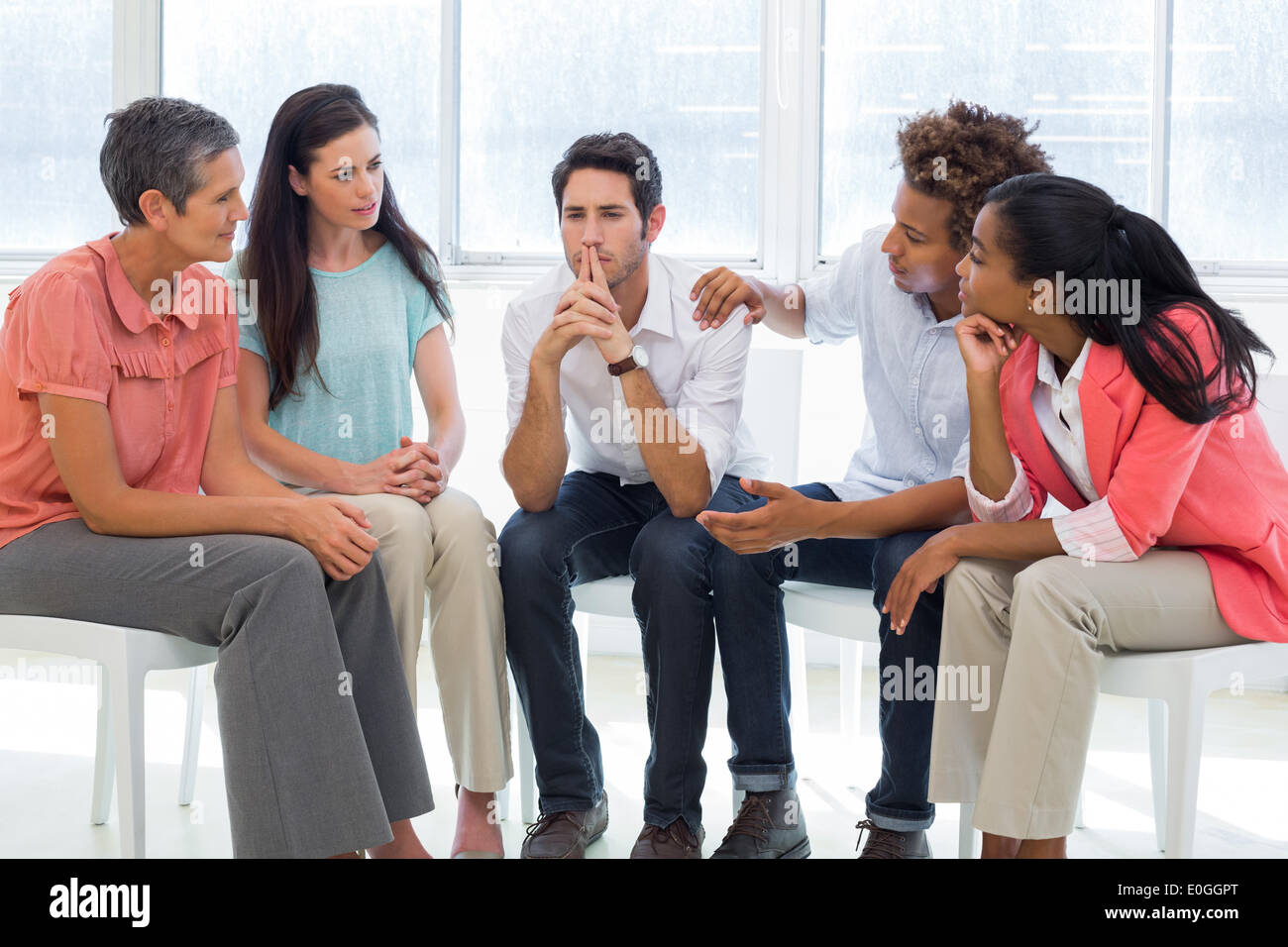Group therapy in session sitting in a circle - Stock Image