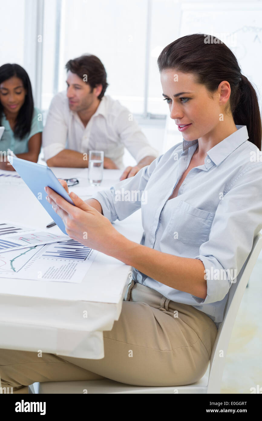 Pretty businesswoman using tablet device in business meeting - Stock Image