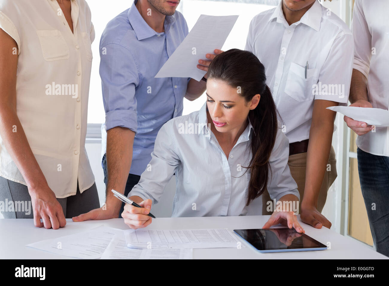 Attractive businesswoman working with businessmen - Stock Image