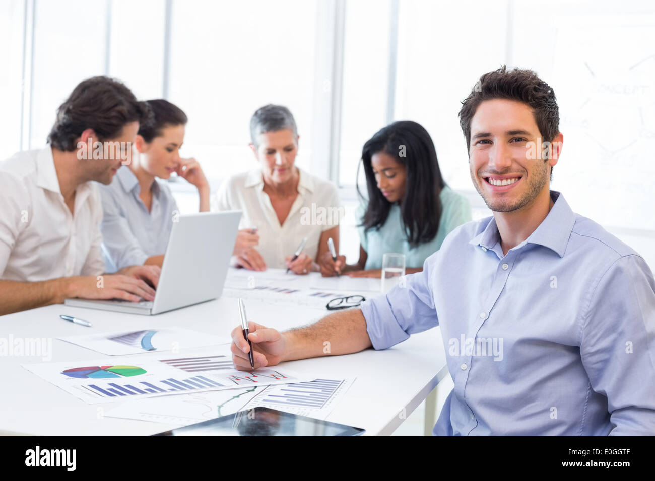 Handsome businessman smiling at the workplace - Stock Image