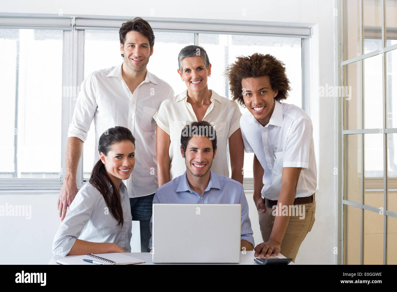 Attractive business people smiling in the workplace - Stock Image