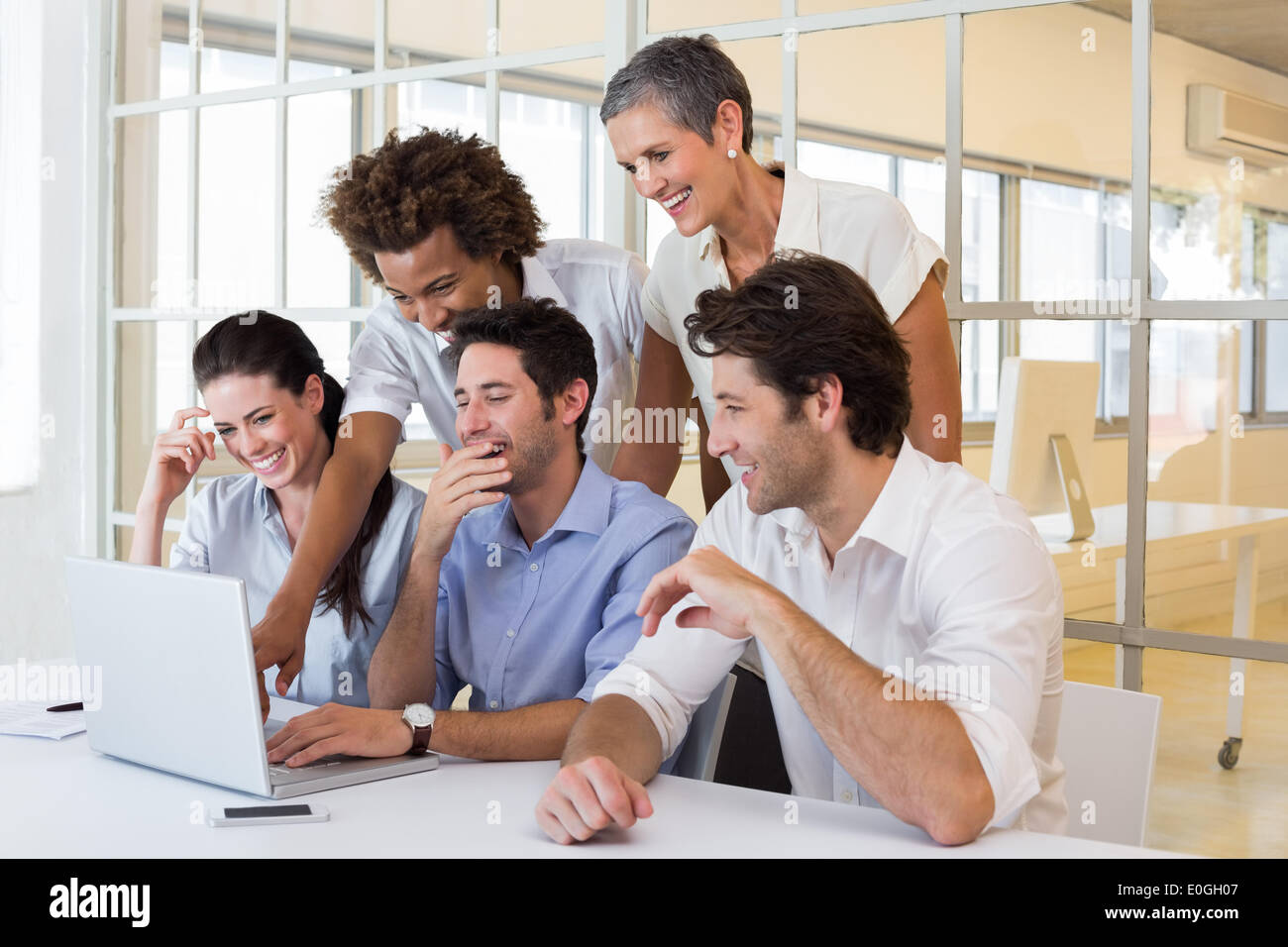 Business people laugh while looking at laptop - Stock Image