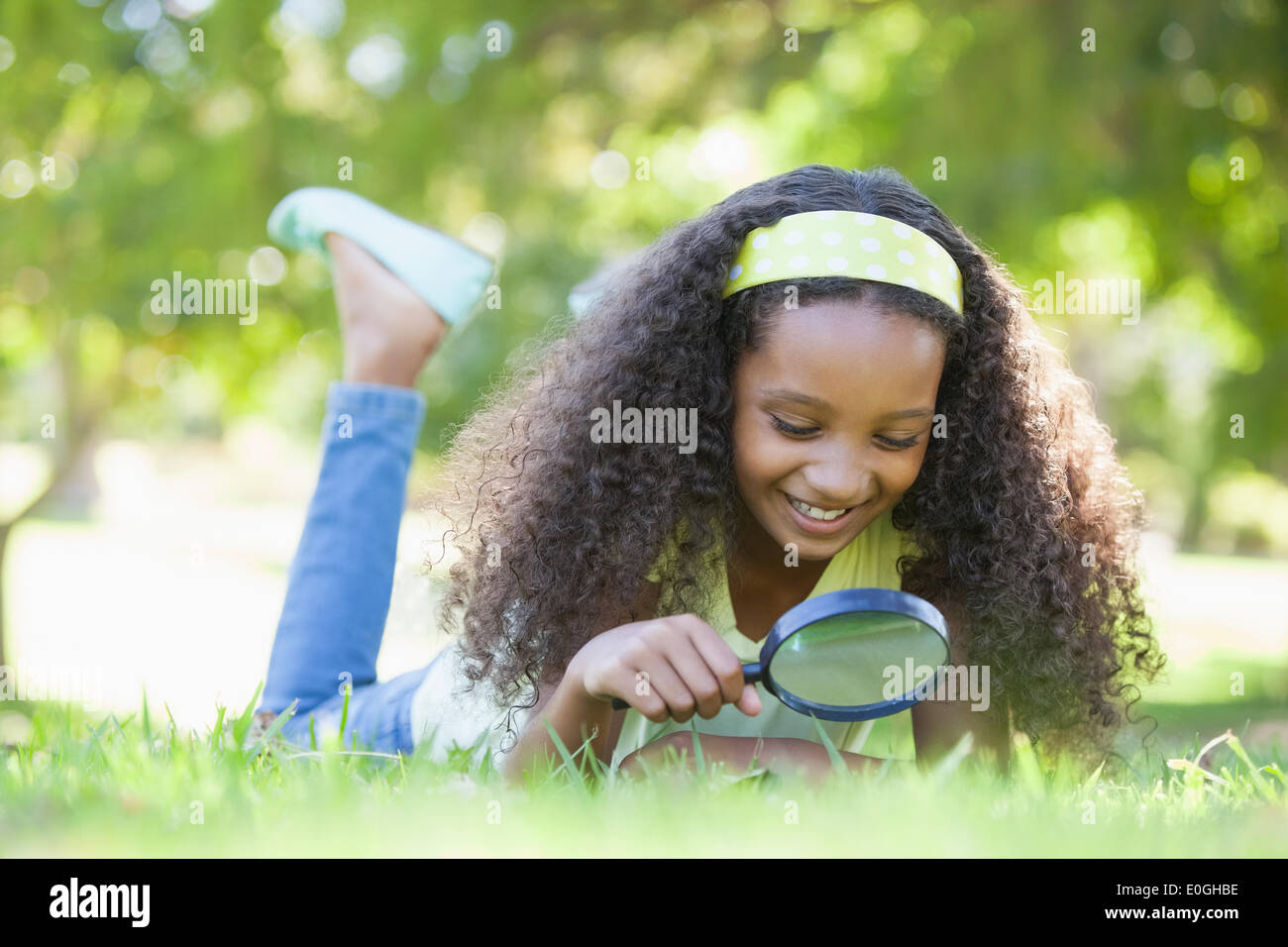 Young girl looking at grass through magnifying glass in the park - Stock Image
