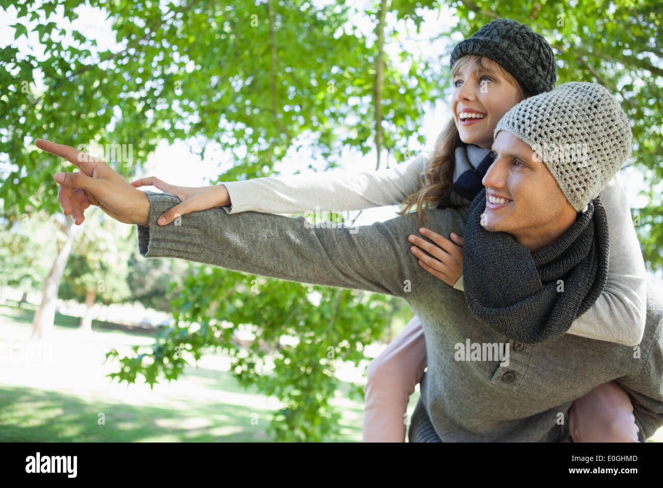 Man giving his pretty girlfriend a piggy back and pointing in the park - Stock Image