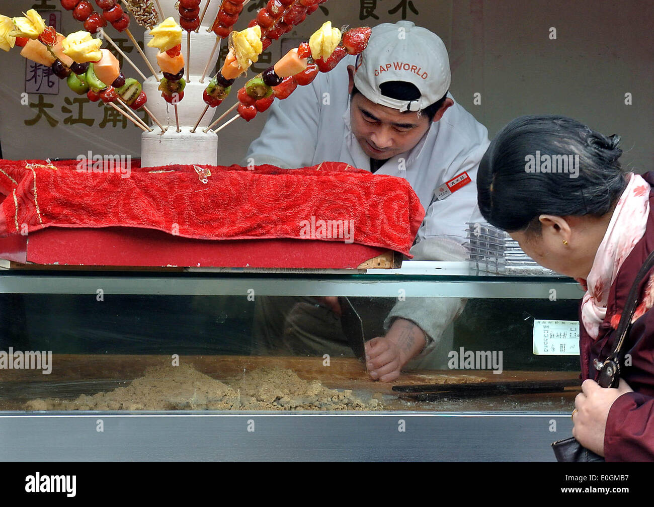 (140513) -- BEIJING, May 13, 2014 (Xinhua) -- Photo taken on Nov. 28, 2013 shows a worker serving peanut candy for a customer in Fuzhou, capital of southeast China's Fujian Province.   One of the most popular types worldwide, Chinese food is famous for its taste and variety, with an unparalleled range of ingredients, techniques, dishes and eating styles. The history of Chinese food stretches back for thousands of years and has changed from period to period and in each region according to climate, tradition and local preferences. Chinese people pride themselves on eating a wide variety of foods - Stock Image