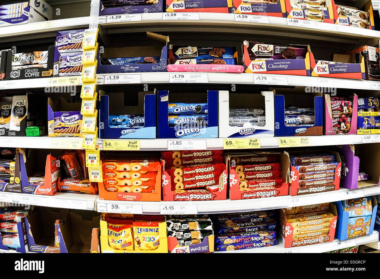 Shelves of packets of biscuits on display in a Tesco supermarket. Stock Photo