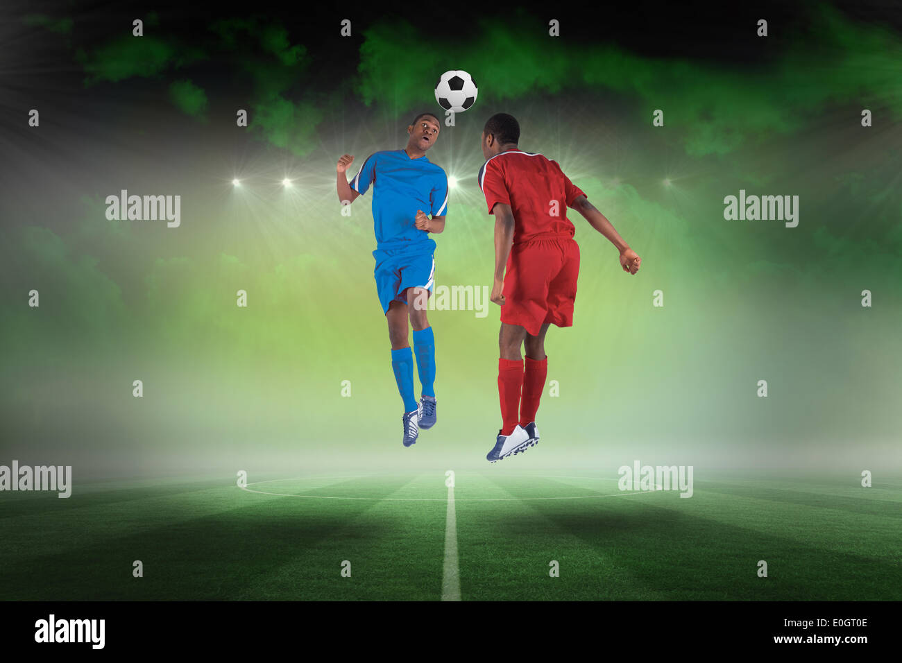 Football players tackling for the ball - Stock Image