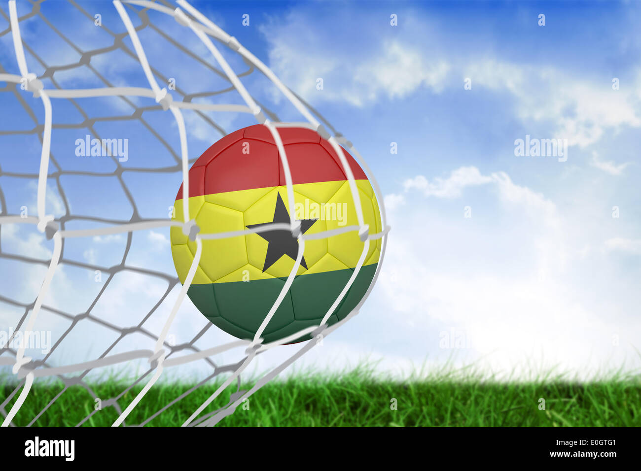 Football in ghana colours at back of net - Stock Image