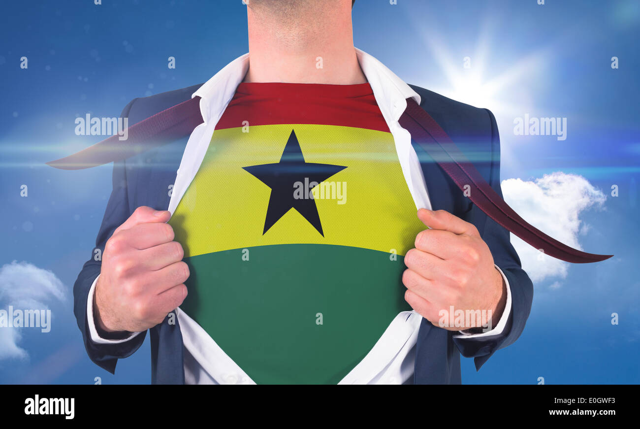 Businessman opening shirt to reveal ghana flag - Stock Image