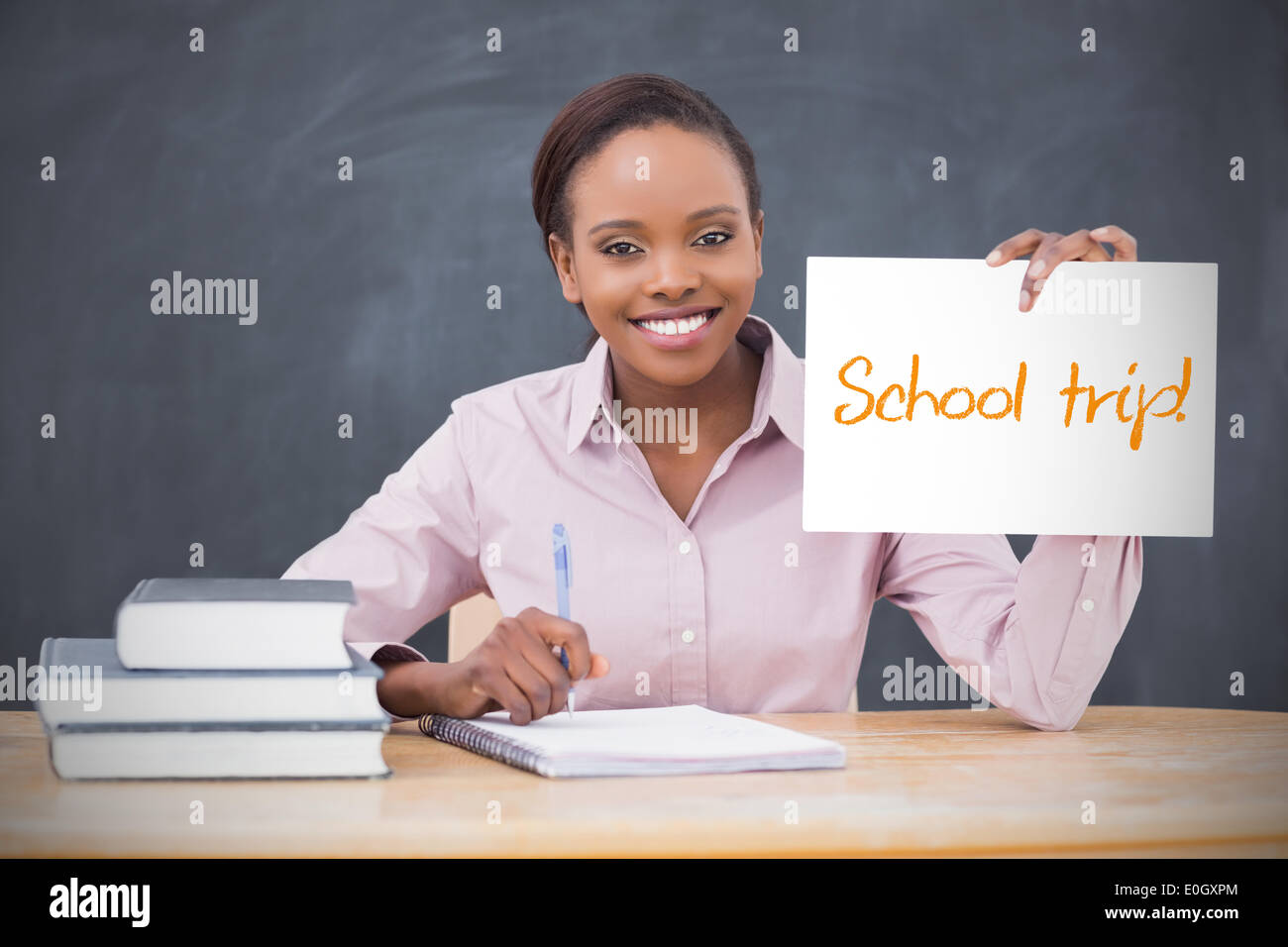 Happy teacher holding page showing school trip - Stock Image