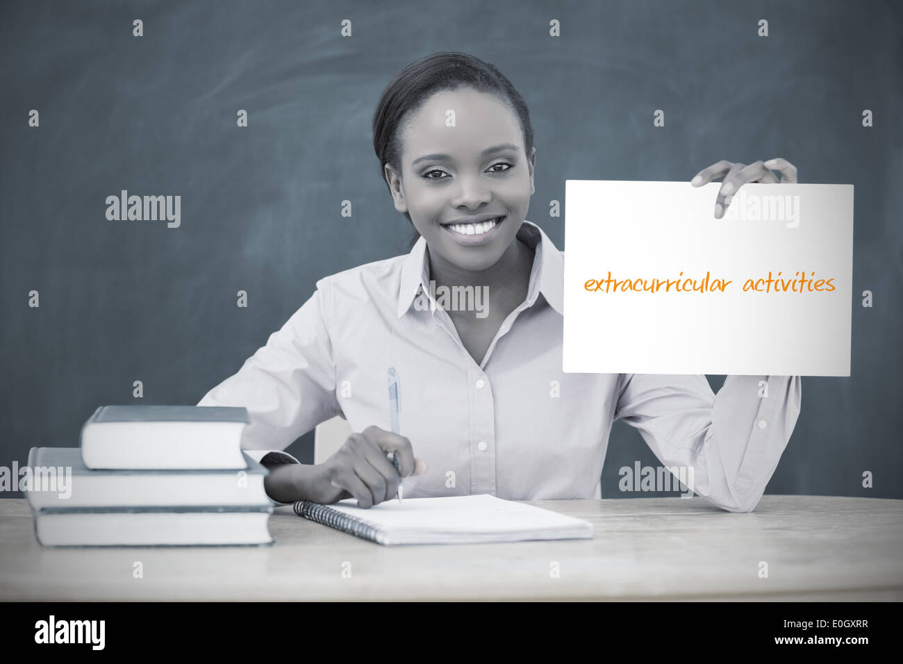 Happy teacher holding page showing extracurricular activities - Stock Image