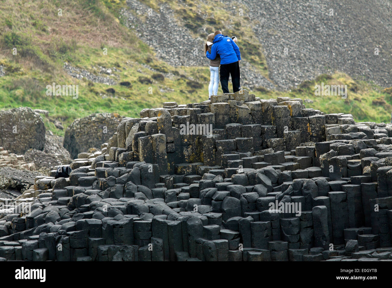 Couple standing on basalt stones at the Giant's Causeway, County Antrim, Northern Ireland, UK, a UNESCO World Heritage Site. - Stock Image