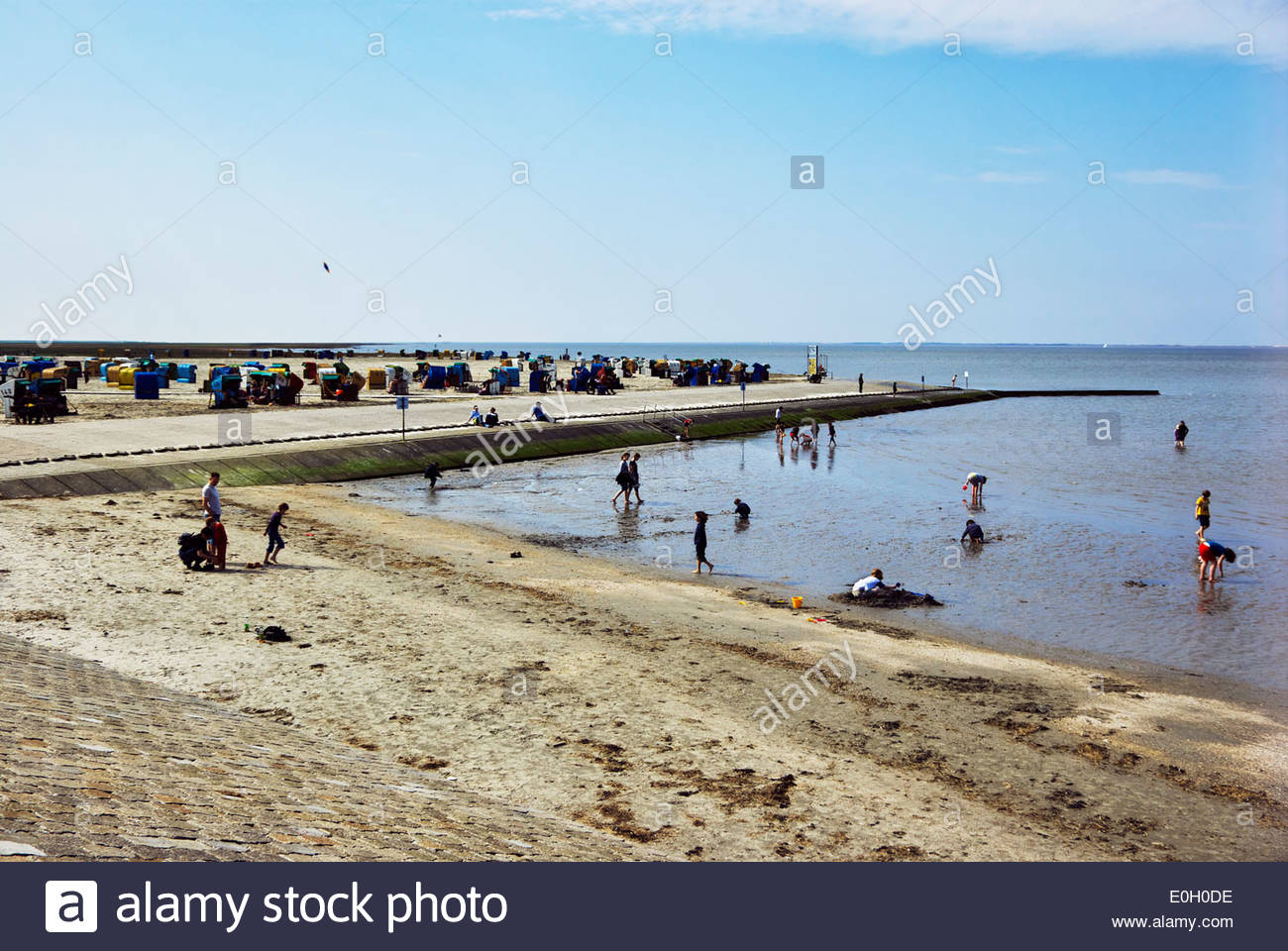 Families play in mud of the Wattenmeer as others relax in Strandkörbe on imported sand at the 'beach' at Neßmersiel, Germany. - Stock Image