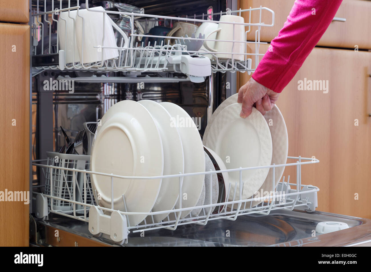 Everyday daily scene of a woman emptying a fitted dishwasher full of clean washed dishes in a domestic kitchen at home UK, Britain - Stock Image