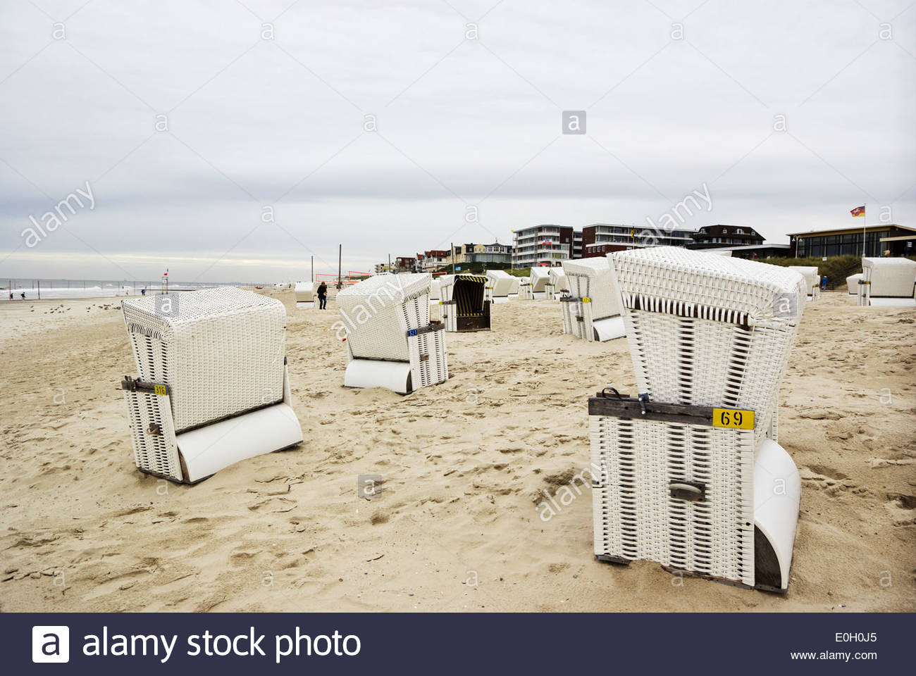 Strandkörbe on the beach at Wangerooge, sea-facing hotels in the distance. - Stock Image