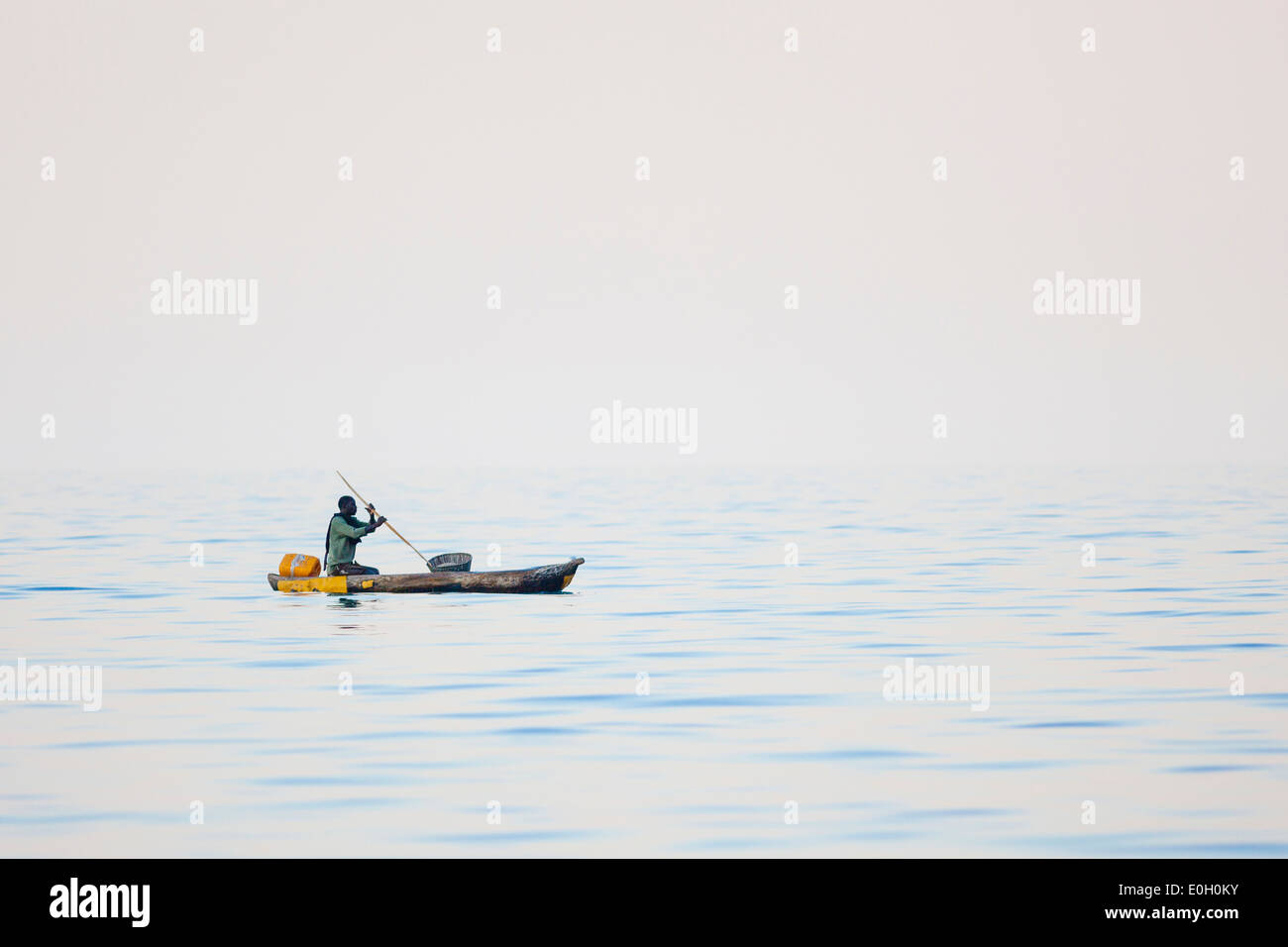 A man in a Dugout, a wooden canoe on Lake Malawi, Malawi, Africa - Stock Image