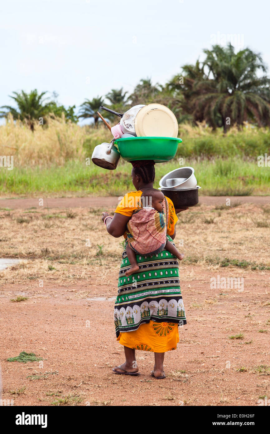 Local woman carrying baby and dishes to the lake to wash up, lake Tanganyika, Mahale Mountains National Park, Tanzania, East Afr - Stock Image