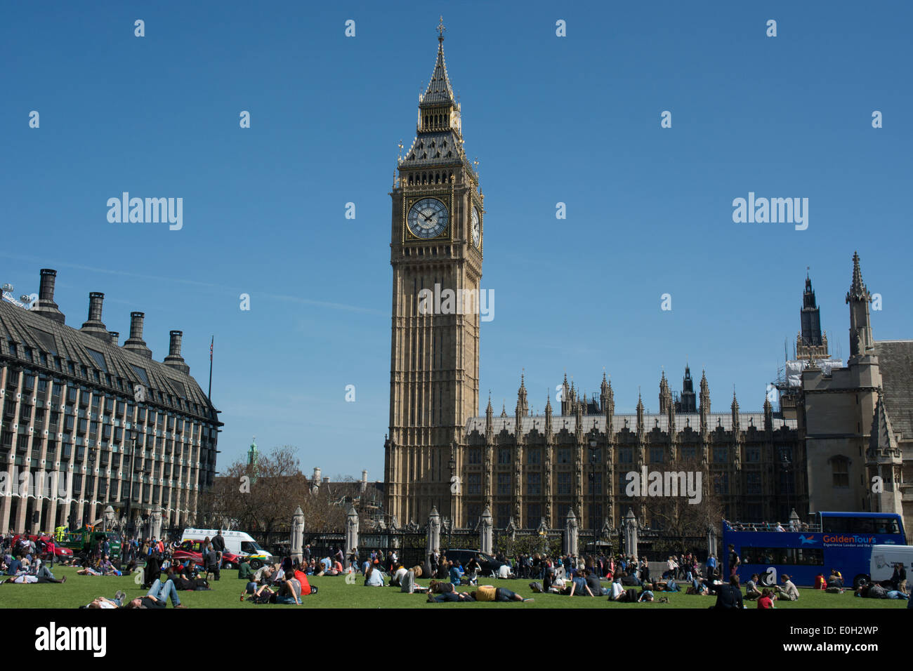 Tourist enjoy a warm spring time day in London on the grass in the center of Parliament Square - Stock Image