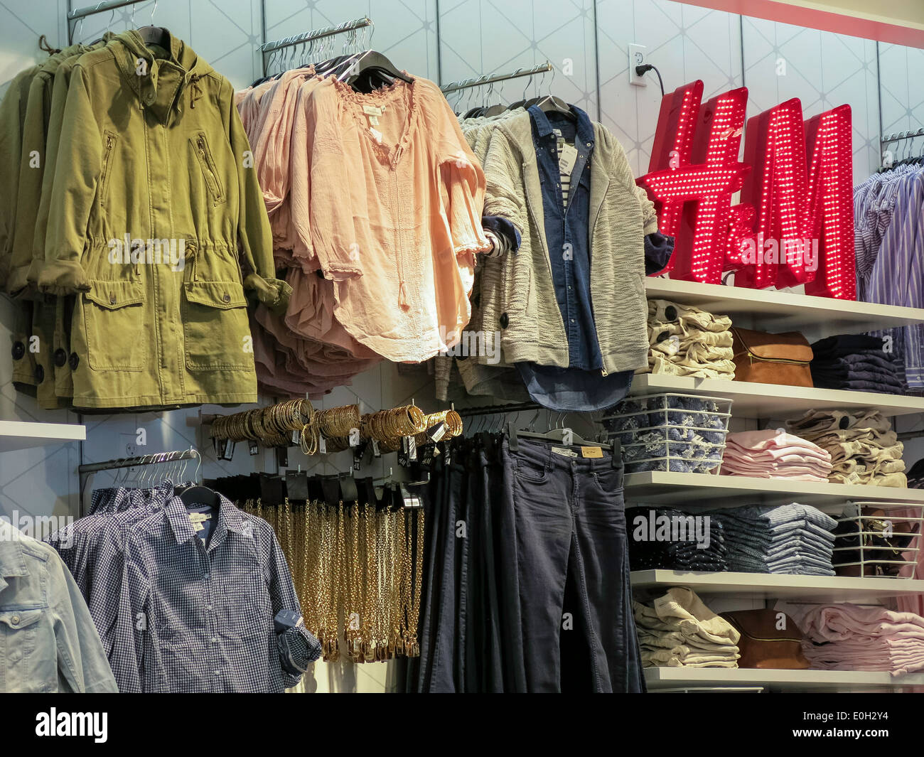 Shelving , Hanging Goods and Logo, H&M Clothing Store Interior in Times Square, NYC, USA - Stock Image