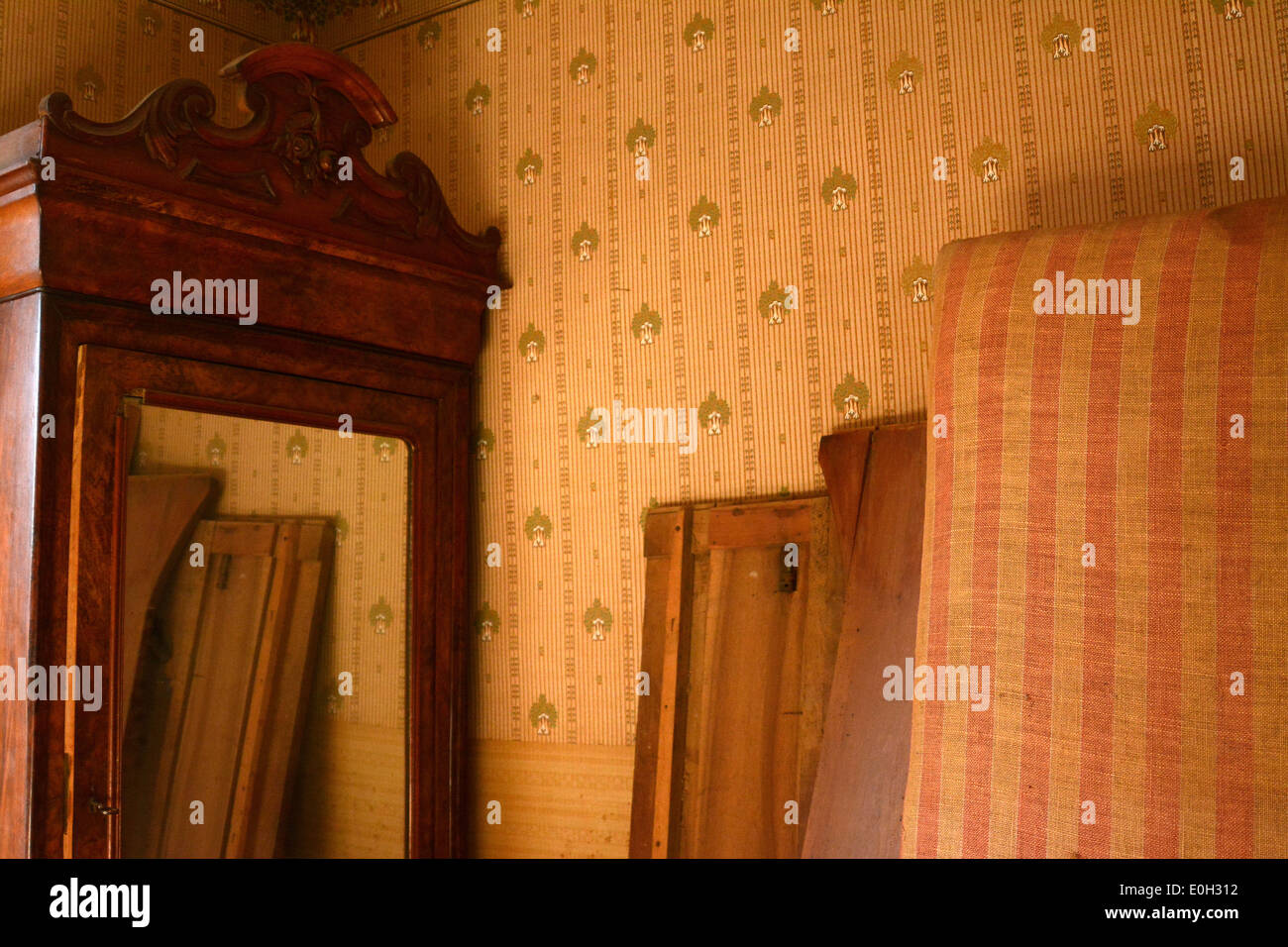 Old furniture, wardrobe and mattresses in an attic - Stock Image