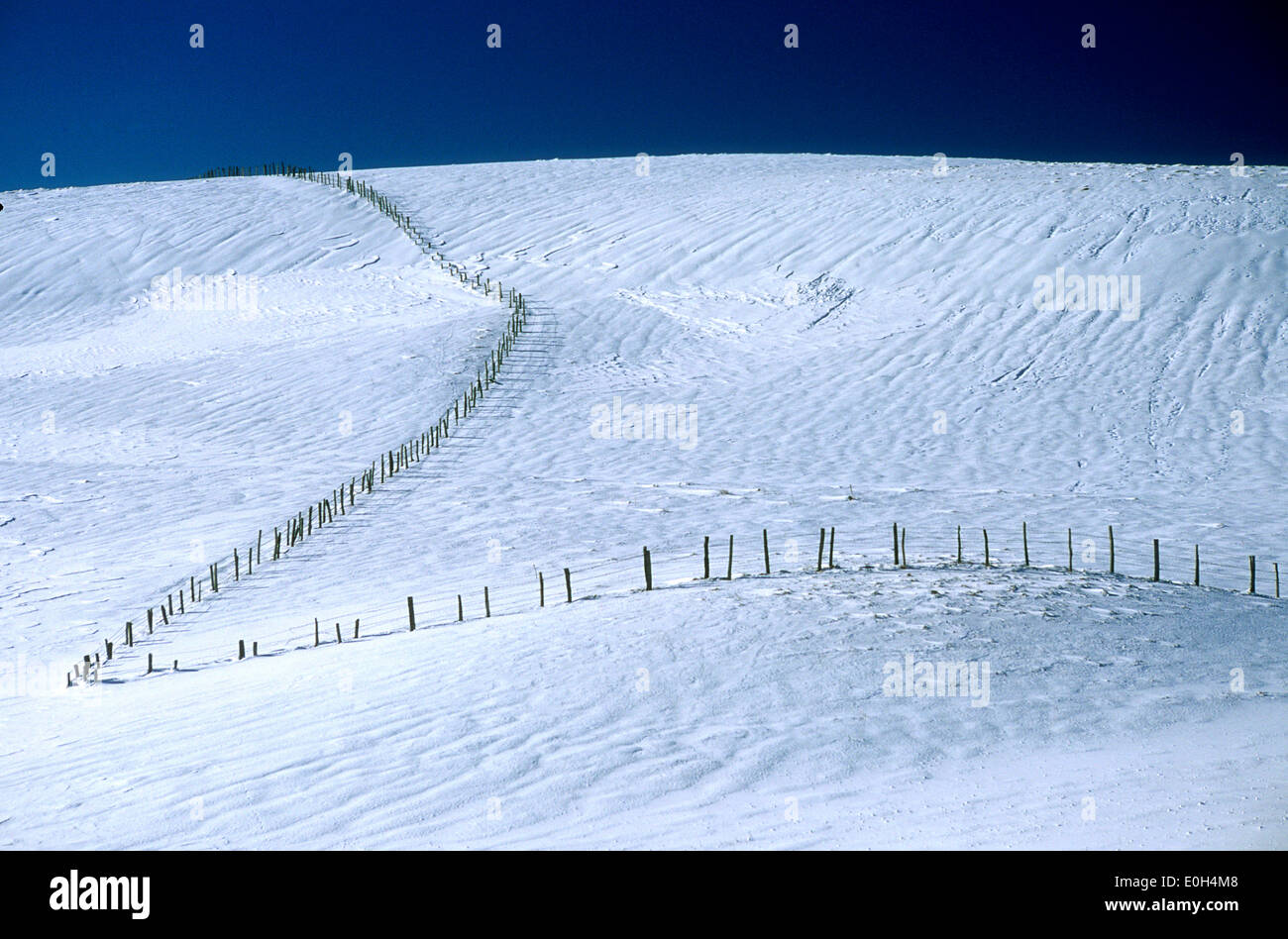 Hillside with snow in winter and fence line - winter landscape snow scene - Stock Image