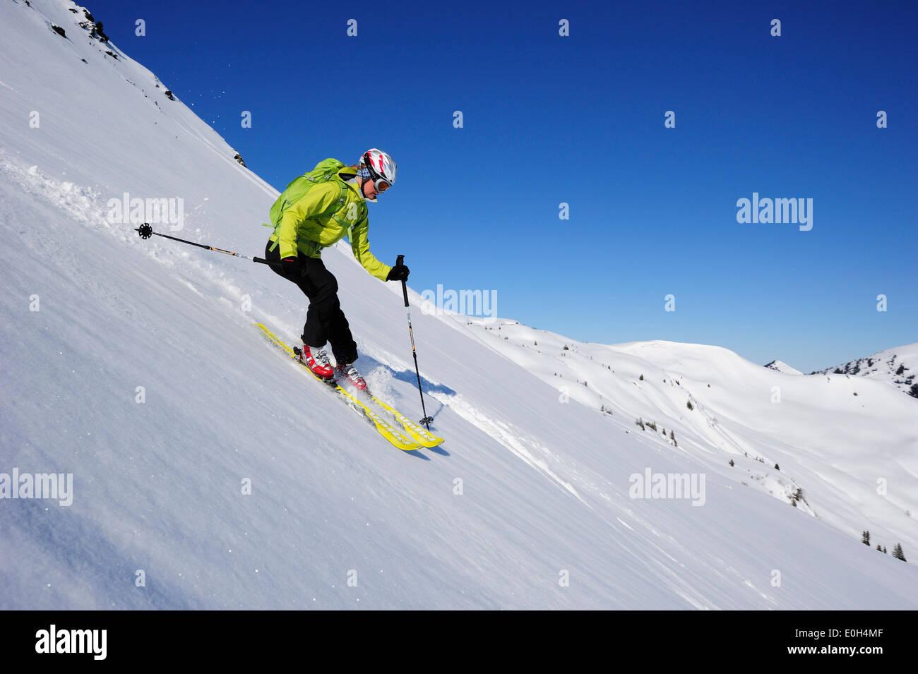Female backcountry skier downhill skiing from Brechhorn, Kitzbuehel Alps, Tyrol, Austria - Stock Image
