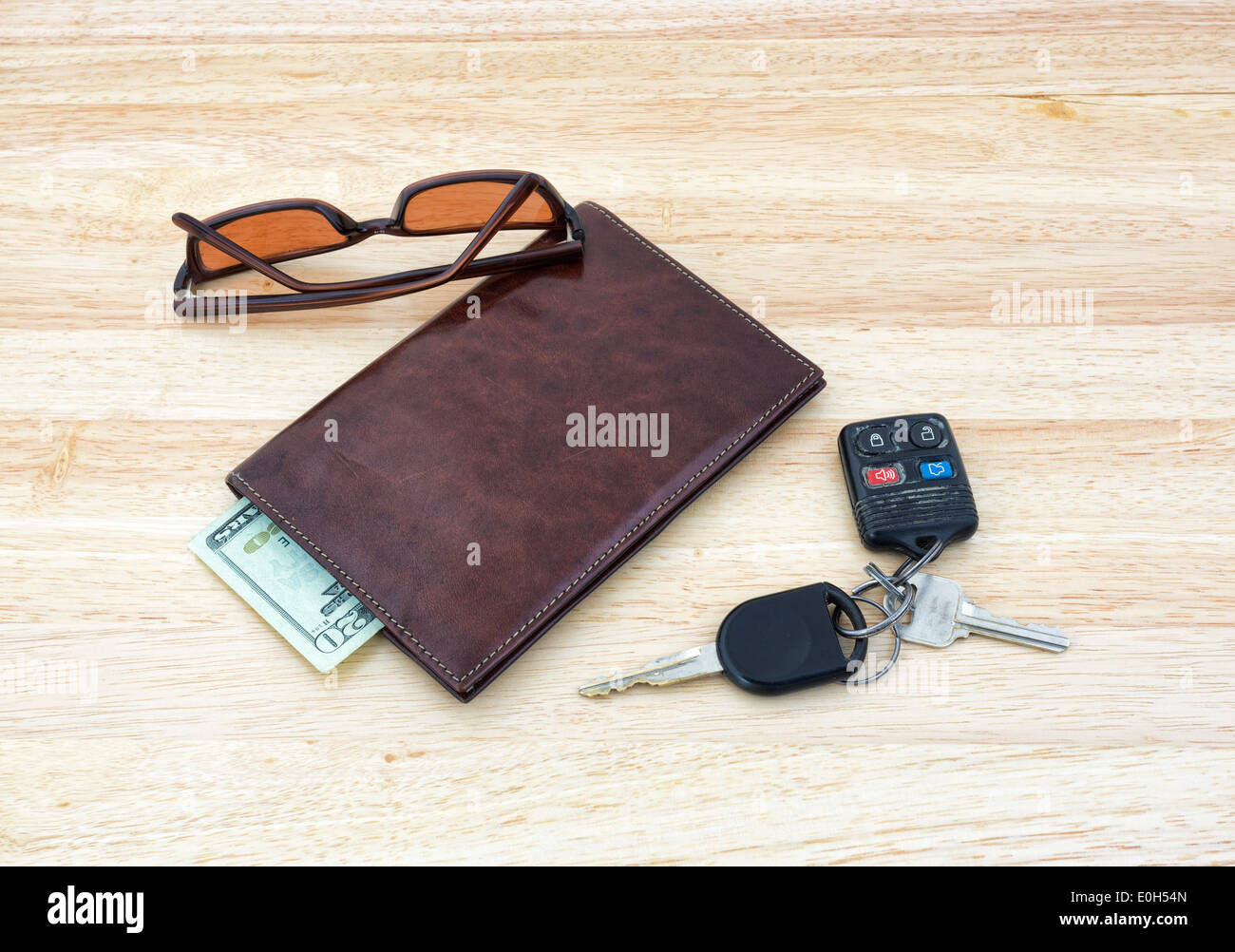 A set of car keys with sunglasses on a wood tabletop with a leather wallet and cash. - Stock Image