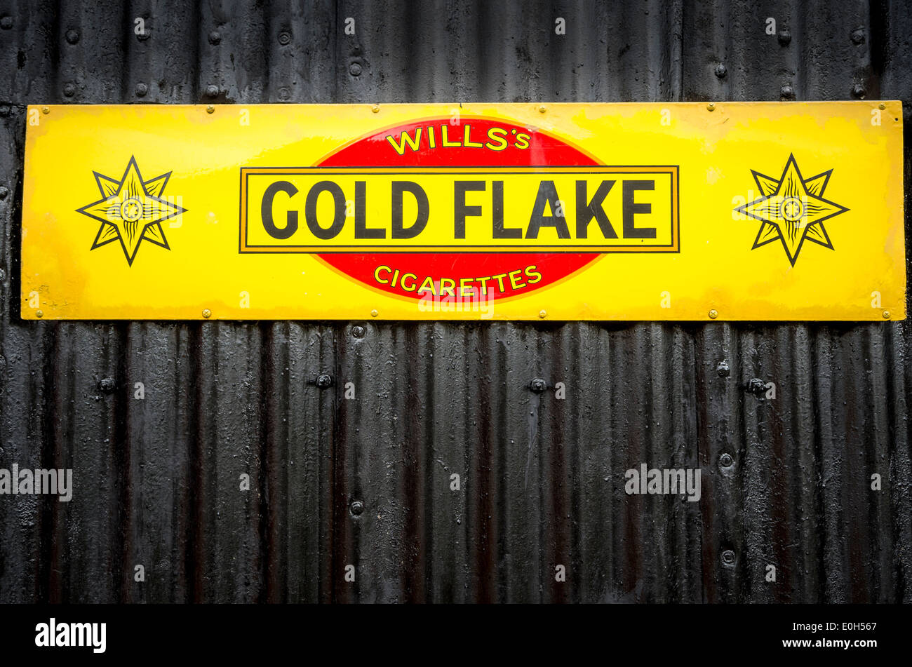 Old metal advertisement for GOLD FLAKE tobacco and cigarettes - Stock Image