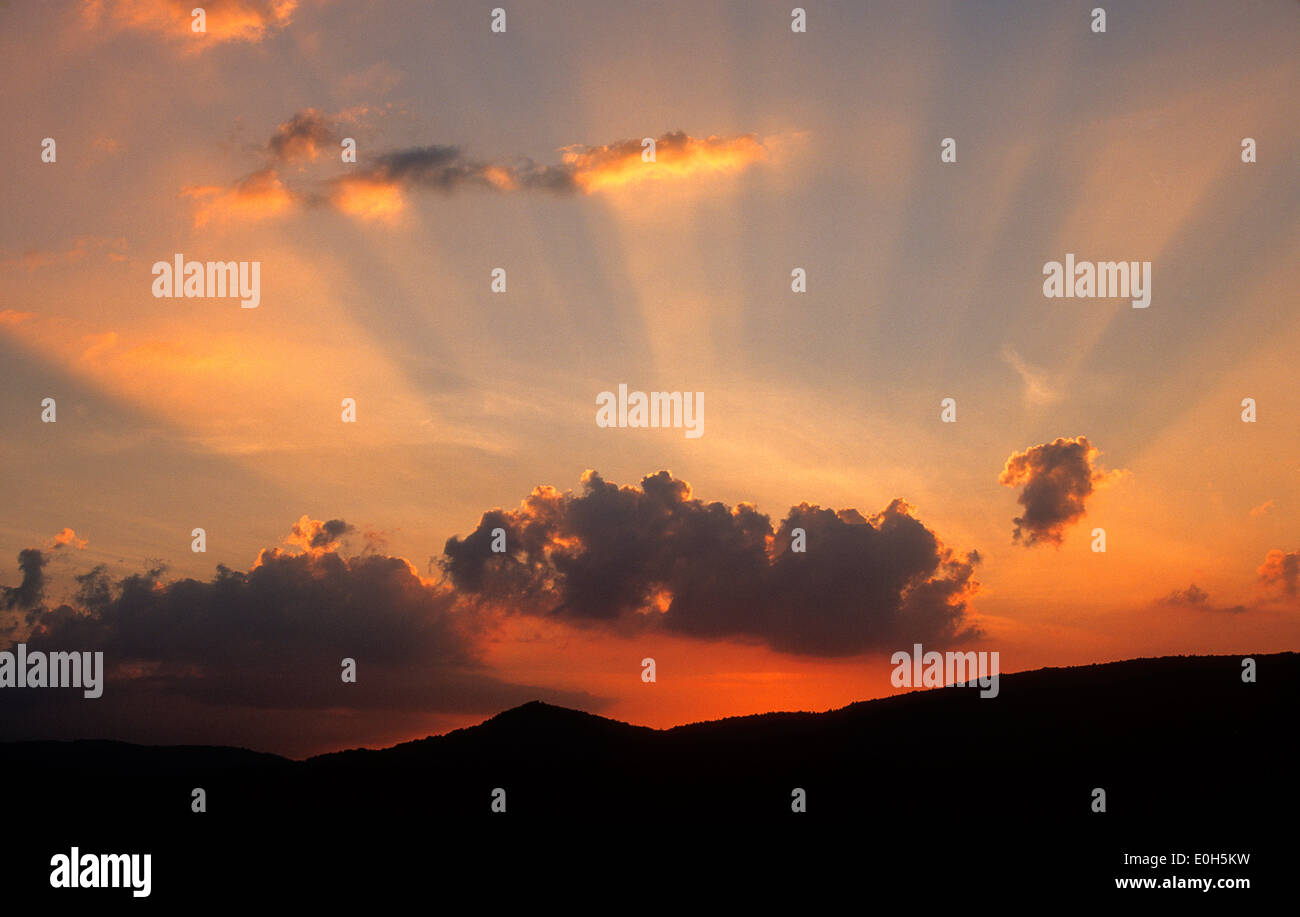 Sunset with clouds, sunbeams and sun rays - Stock Image