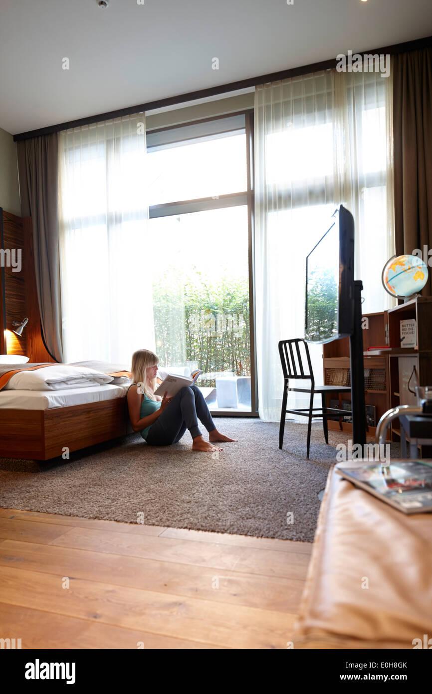 Woman sitting on floor of a hotel room, Hafencity, Hamburg, Germany - Stock Image
