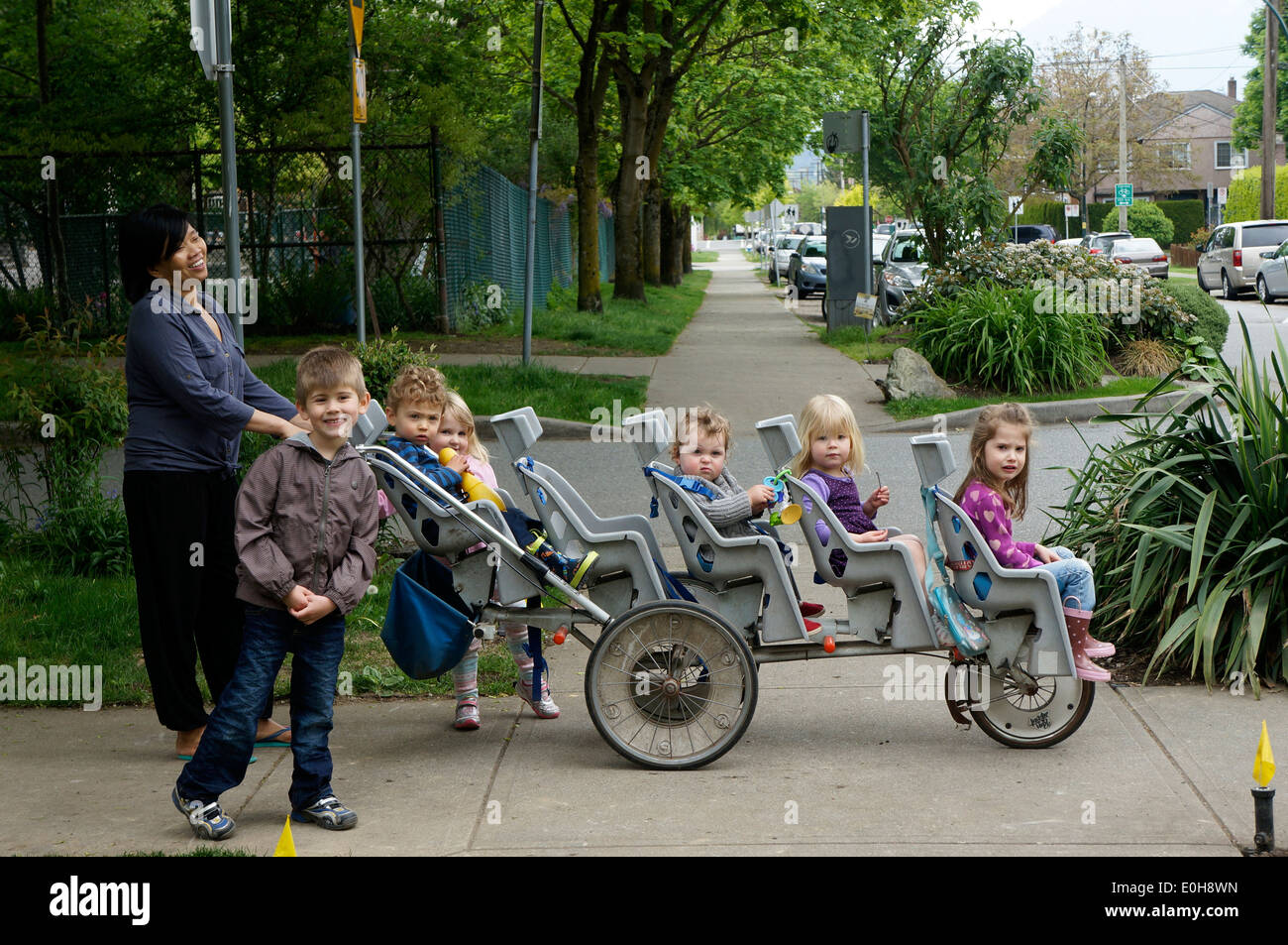 Asian nanny pushing a multi-seat, multi-child stroller, Vancouver, BC, Canada - Stock Image