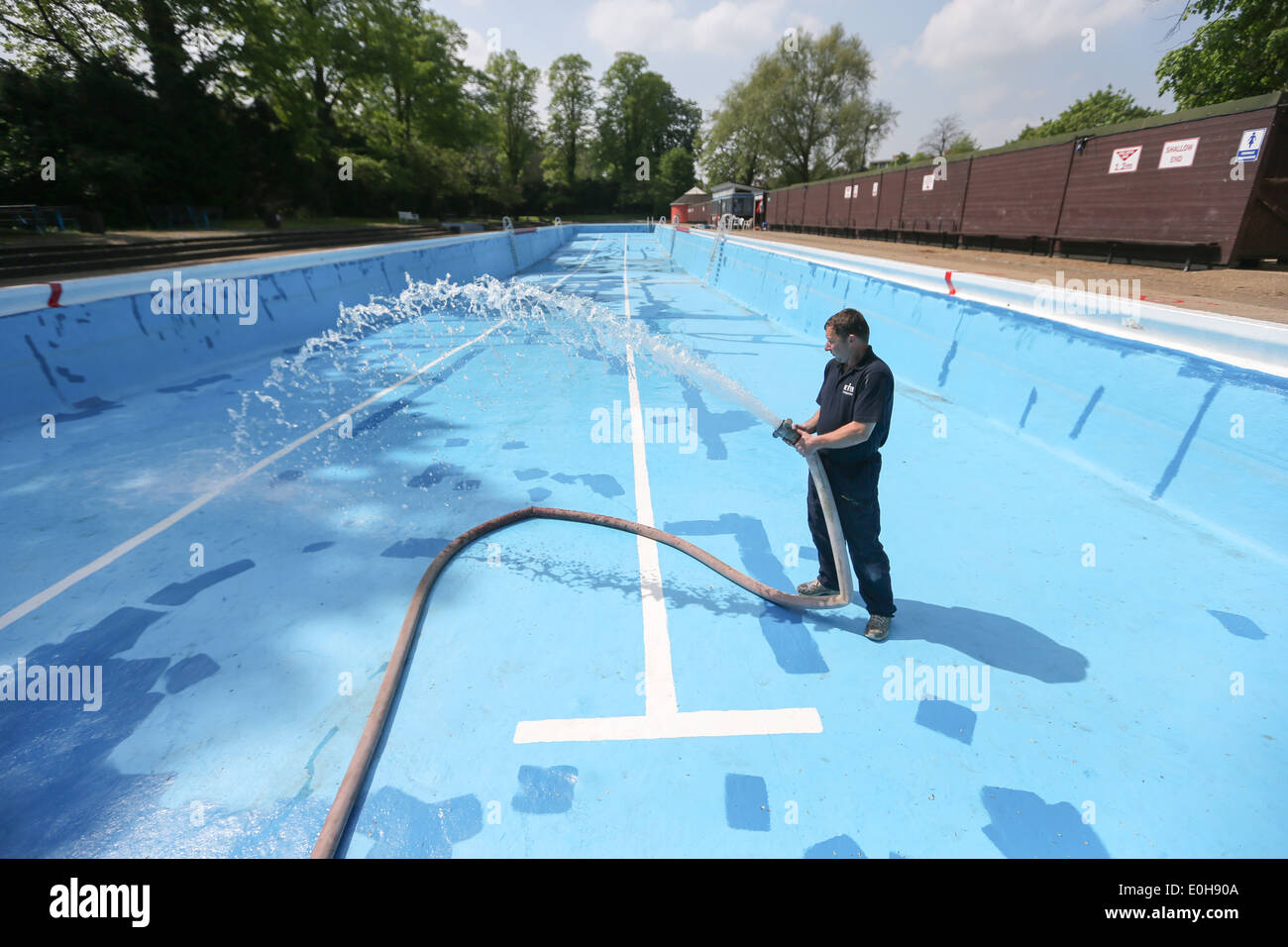 A man filling an outdoor swimming pool with a hose Stock ...