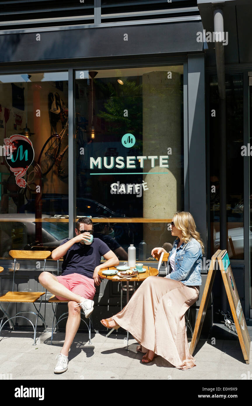 Man and woman sitting outside the Musette Caffe on Pender Street in Chinatown Downtown Eastside, Vancouver, BC, Canada - Stock Image